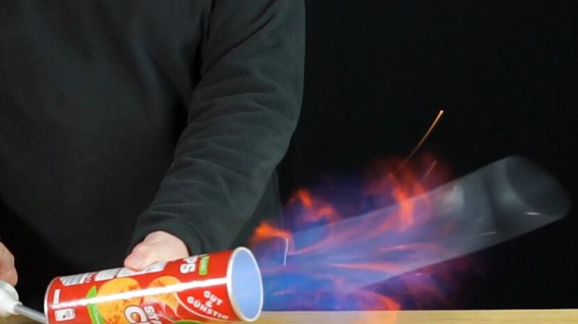 Das Benzin explodiert in der Chipspackung, der Überdruck schießt den Deckel weg und überschüssiges Benzin verbrennt als kleine Stichflamme.