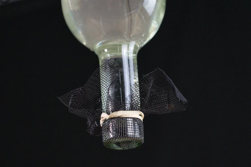 Sogar eine Flasche wird wasserdicht mit einem Netz