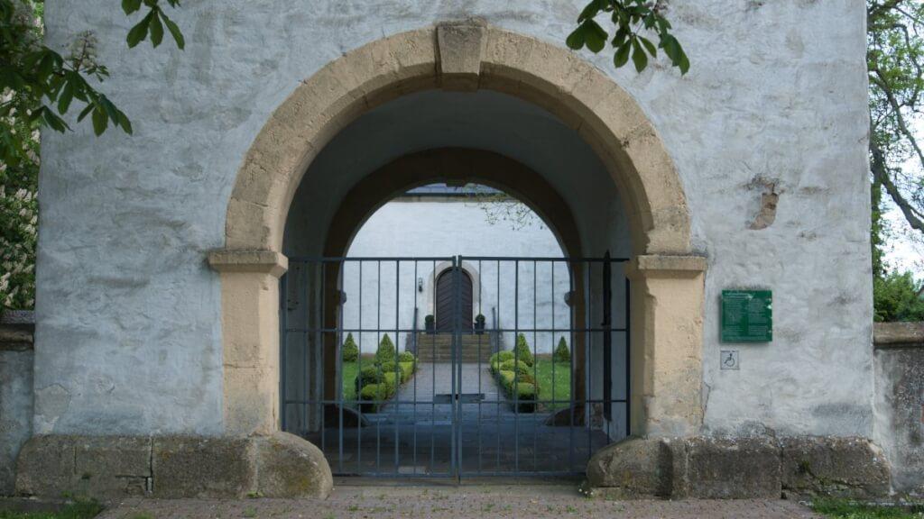 Ein Rundbogen an einem Kirchentor. Die Kräfte durch das Gewicht des Gebäudes, werden gleichmäßig auf das Fundament geleitet.