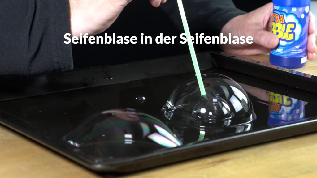 Auf einer Wasseroberfläche kann man sehr leicht eine Seifenblase in einer Seifenblase aufpusten.