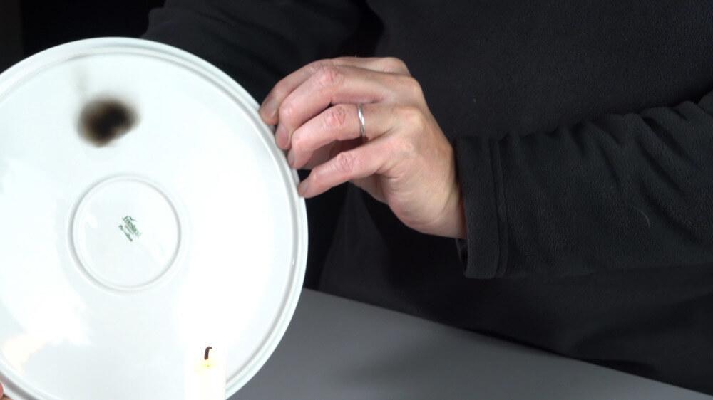Kerzenruß schlägt sich auf einem Porzellanteller nieder.