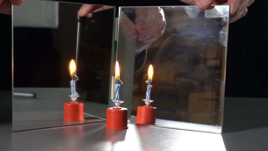 Eine Kerze und zwei Spiegelbilder. Die Spiegel stehen im Winkel von 120°