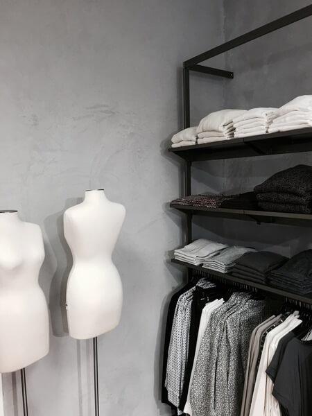 Raum mit Betonwand in monochromem Stil. Präsentation monochromer Kleidung auf schwarzem Metallregal.