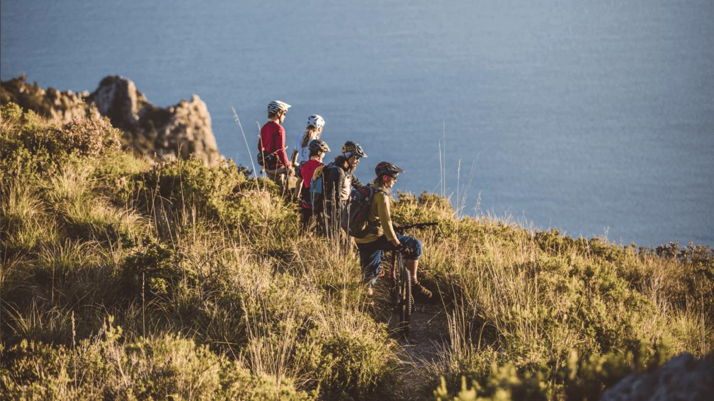 Bei der Mountainbike Reise in der Toskana genießt die Gruppe den Ausblick über das Meer.