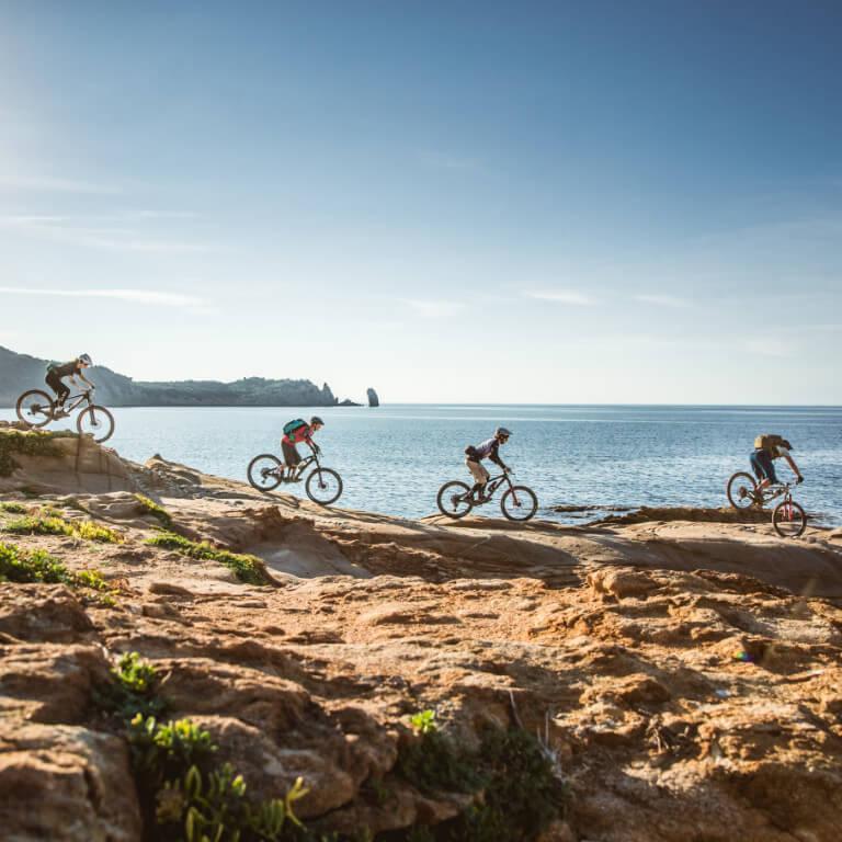 Die Gruppe fährt bei den Mountainbike Reisen in der Toskana auf Felsplatten direkt am Meer