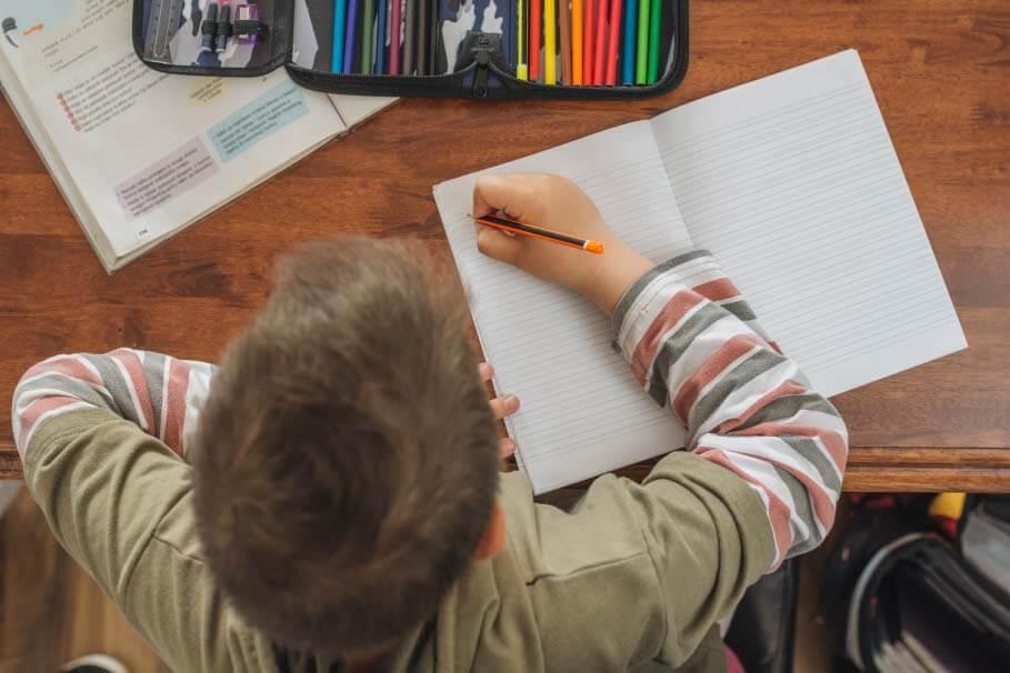 Junge am Hausaufgaben machen   Sorgfaeltig