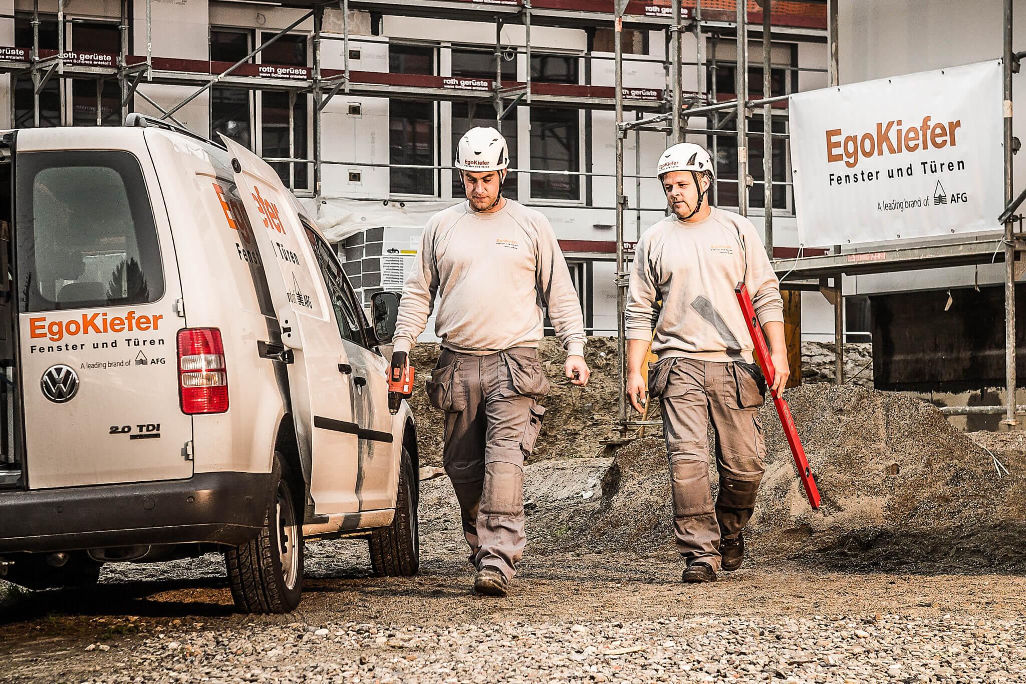 Die Fotografie zeigt Bauarbeiter, die mit Werkzeug in der Hand zum Fahrzeug gehen.