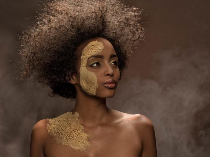 Portrait des Models Eden mit Tonerde im Gesicht.