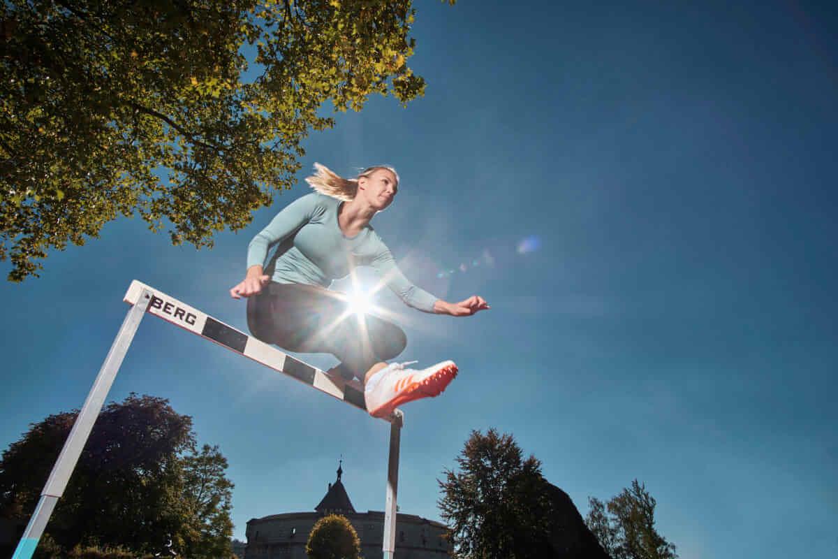 Die Leichtathletin Lydia Boll überspringt die erste Hürde beim Hürdenlauf. Dank HSS-Blitzen ist sie nicht nur als Silhouette sichtbar.