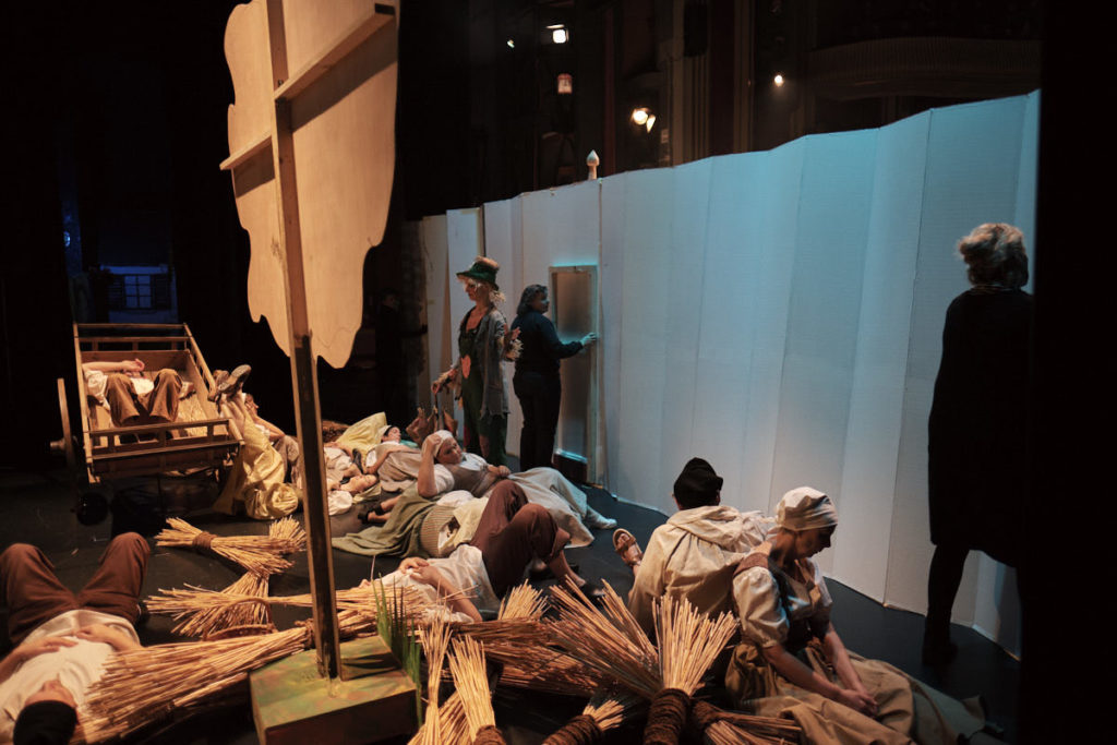 Während im vorderen Teil der Bühne das Stück läuft, bereiten sich hinter dem Paravent die SchauspielerInnen auf die nächste Szene vor.