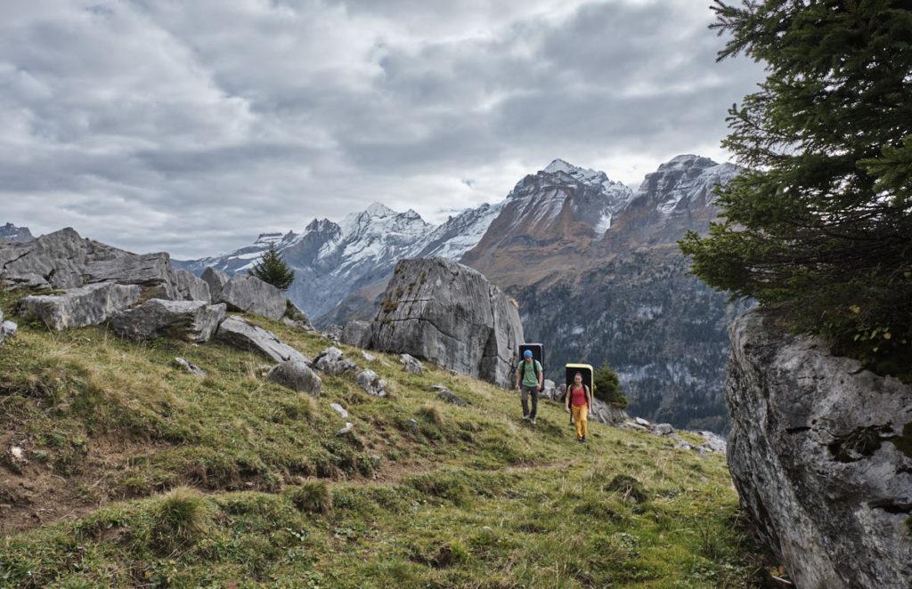Mit den Crash-Pads auf dem Rücken suchen sich die Kletterer einen guten Felsblock.