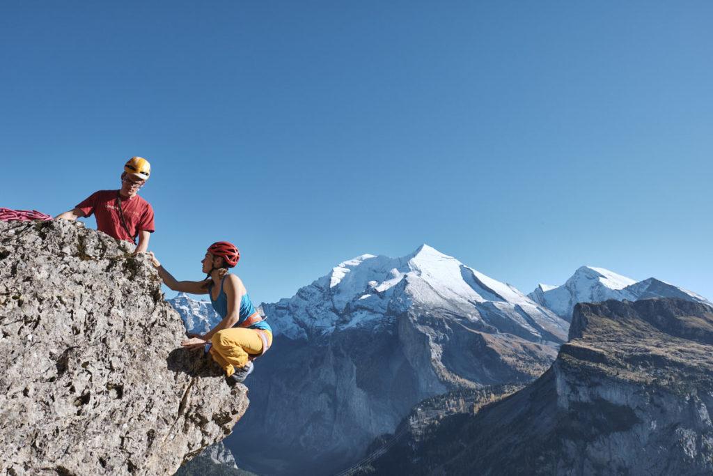 Andrea Kümin und Jonas Allemann klettern an einem Boulder im alpinen Stil.