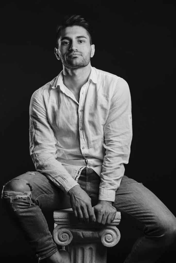 Pietro sitzt auf einer Säule und blickt ernst in die Kamera.