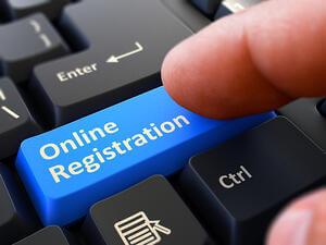 Online Registration Written on Blue Keyboard Key. Male Hand Presses Button on Black PC Keyboard. Closeup View. Blurred Background.