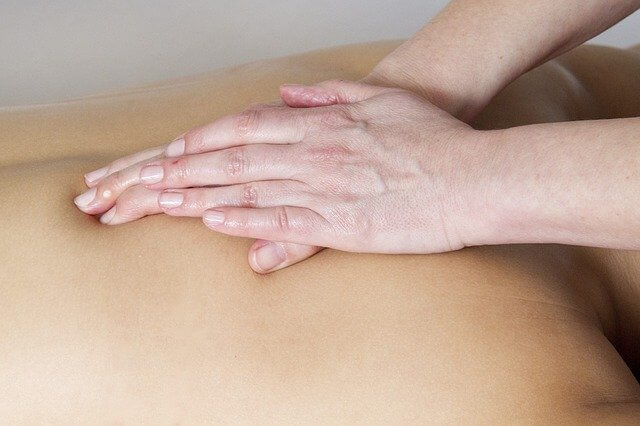Zwei Hände liegen zur Massage auf dem Rücken eines Kunden.